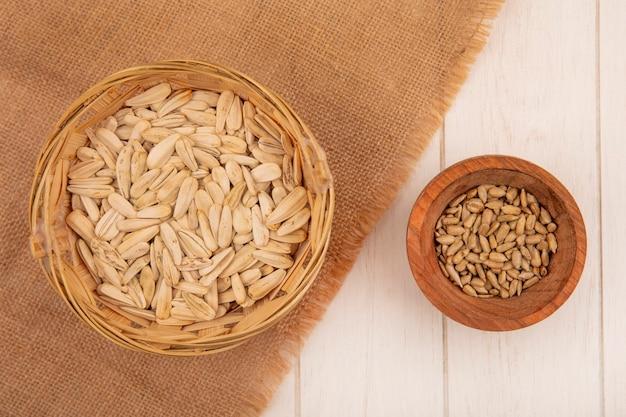 Vue de dessus de savoureuses graines de tournesol blanc salé sur un seau sur un sac en tissu avec des graines de tournesol décortiquées sur un bol en bois sur une table en bois beige