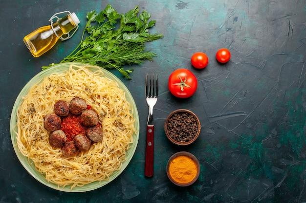 Vue de dessus de savoureuses pâtes italiennes avec des boulettes de viande et différents assaisonnements sur le bureau bleu foncé