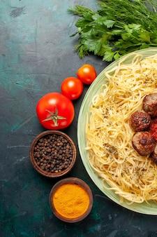 Vue de dessus de savoureuses pâtes italiennes avec des boulettes de viande et différents assaisonnements sur le fond bleu foncé