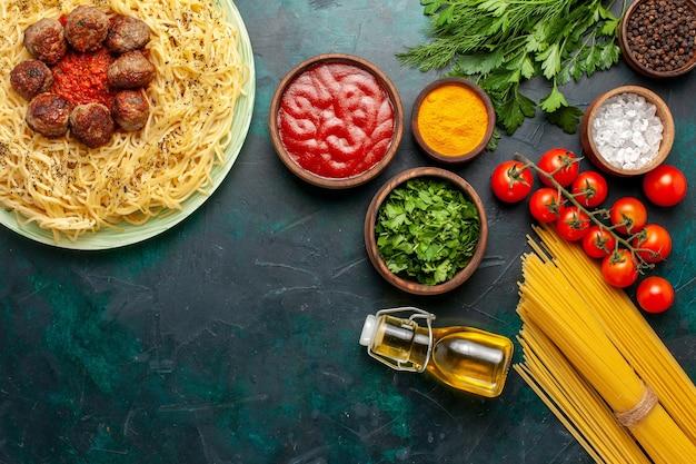 Vue de dessus de savoureuses pâtes italiennes avec des boulettes de viande et différents assaisonnements sur fond bleu