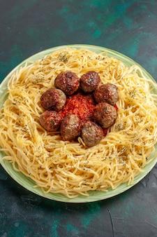 Vue de dessus de savoureuses pâtes italiennes avec des boulettes de viande sur le fond bleu foncé