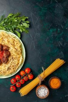 Vue de dessus de savoureuses pâtes italiennes avec des boulettes de viande et des verts sur un bureau bleu foncé