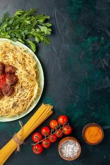 Vue de dessus de savoureuses pâtes italiennes avec des boulettes de viande et des verts sur fond bleu foncé