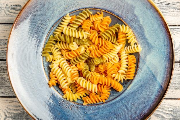 Vue de dessus de savoureuses pâtes italiennes pâtes en spirale cuites inhabituelles sur bois gris