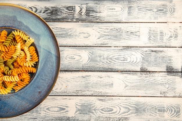 Vue de dessus de savoureuses pâtes italiennes pâtes en spirale cuites inhabituelles sur un bureau en bois gris