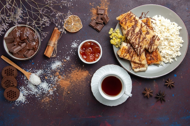Vue de dessus de savoureuses pâtisseries sucrées avec du thé et du fromage cottage sur fond sombre pâtisserie biscuit gâteau sucre thé sucré