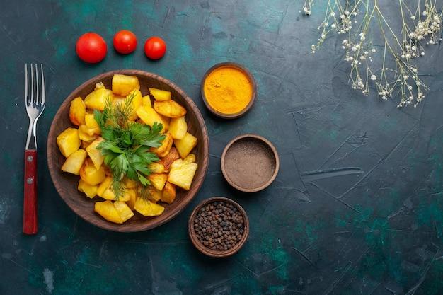 Vue de dessus savoureuses pommes de terre cuites avec assaisonnements sur fond bleu foncé