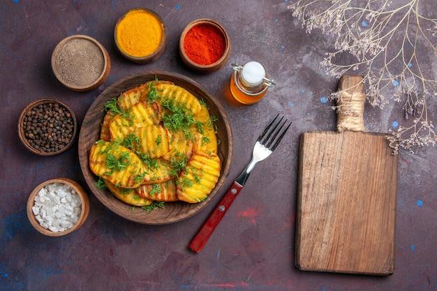 Vue de dessus de savoureuses pommes de terre cuites avec des légumes verts et différents assaisonnements sur une surface sombre dîner repas plat cips cuisson de pommes de terre