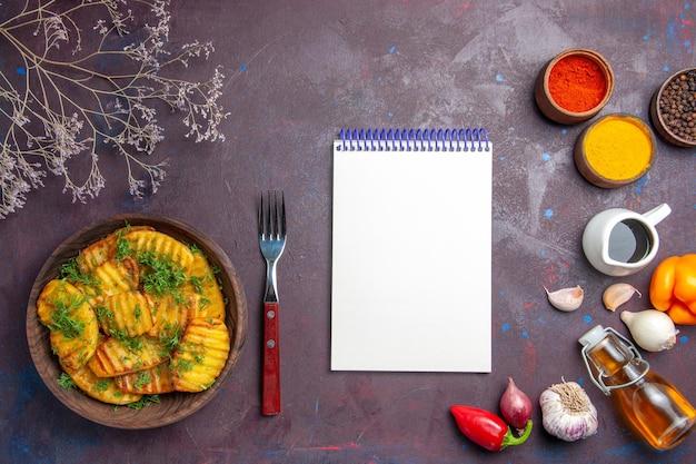Vue de dessus de savoureuses pommes de terre cuites avec des légumes verts sur la surface sombre plat de repas du dîner cuisson des pommes de terre