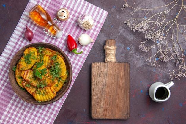 Vue de dessus savoureuses pommes de terre cuites plat délicieux avec des légumes verts sur la surface sombre dîner de pommes de terre cuisine repas plat