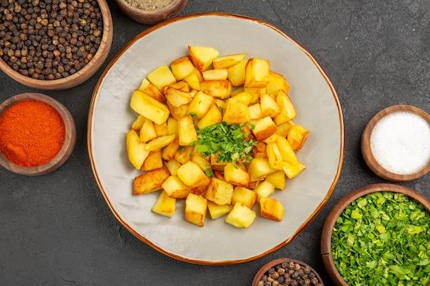 Vue de dessus de savoureuses pommes de terre frites à l'intérieur de la plaque avec des assaisonnements sur une surface sombre
