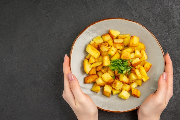 Vue de dessus de savoureuses pommes de terre frites à l'intérieur de la plaque avec des verts sur la surface sombre