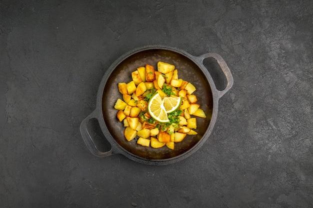 Vue de dessus de savoureuses pommes de terre frites à l'intérieur de la poêle avec des tranches de citron sur la surface sombre