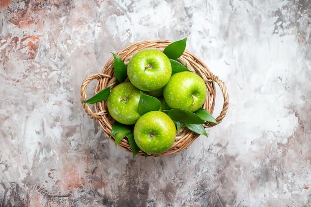 Vue de dessus de savoureuses pommes vertes à l'intérieur du panier sur le fond clair
