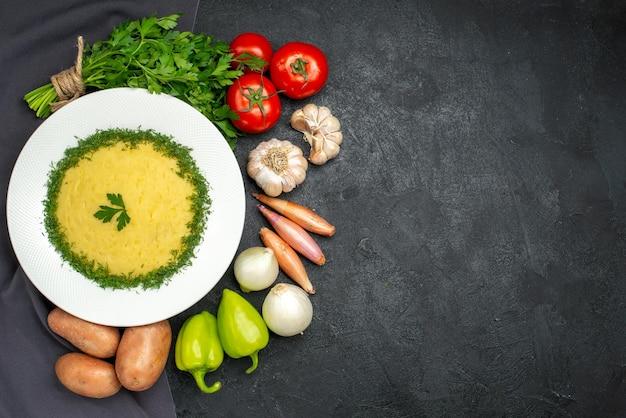 Vue de dessus de savoureuses purées de pommes de terre avec des légumes verts et des légumes frais sur fond noir