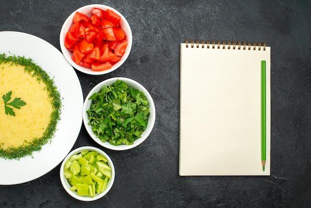 Vue de dessus de savoureuses purées de pommes de terre avec des légumes verts et des tranches de tomates fraîches sur fond gris