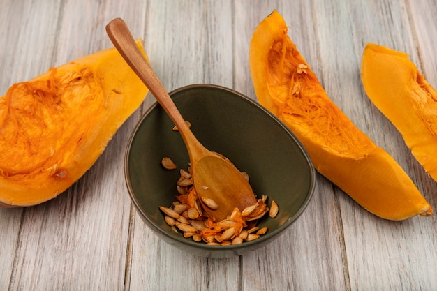 Vue de dessus de savoureuses tranches de citrouille orange avec des graines sur un bol avec une cuillère en bois sur une surface en bois gris