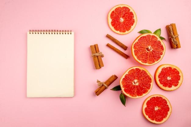 Vue de dessus de savoureuses tranches de fruits de pamplemousse à la cannelle sur la surface rose