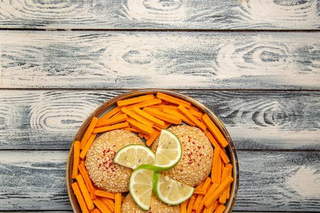 Vue de dessus de savoureux biscuits avec des tranches de citron et des biscottes sur le bureau gris rustique biscuit gâteau au sucre biscuit sucré