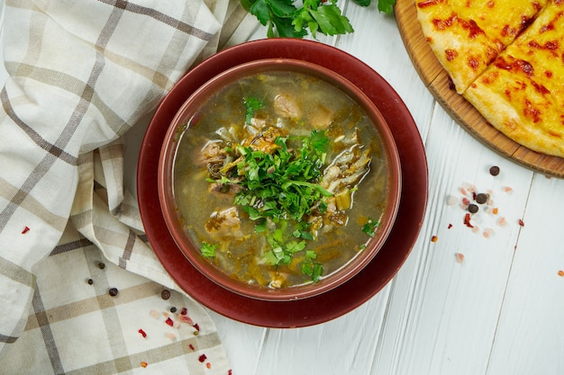 Vue de dessus sur de savoureux chakapuli - ragoût géorgien traditionnel avec des côtelettes d'agneau ou du veau, des oignons, des feuilles d'estragon, des prunes cerises ou du tkemal dans une assiette en céramique. fond en bois