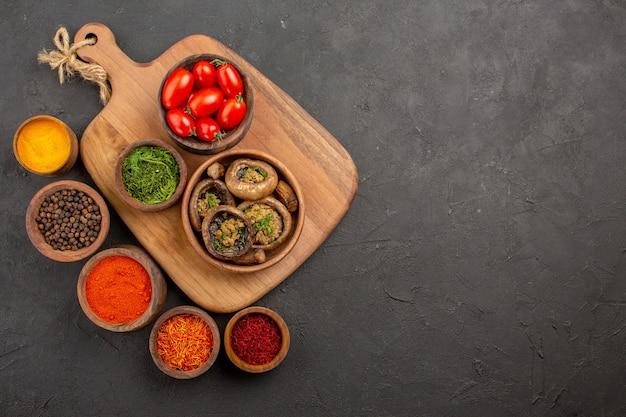 Vue de dessus savoureux champignons cuits avec des tomates sur fond sombre