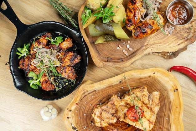 Vue de dessus savoureux cou de porc grillé. ailes de poulet et saucisses mur en bois. copiez l'espace.