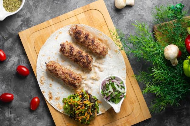 Vue de dessus d'un savoureux kebab de lyulya sur une assiette en bois