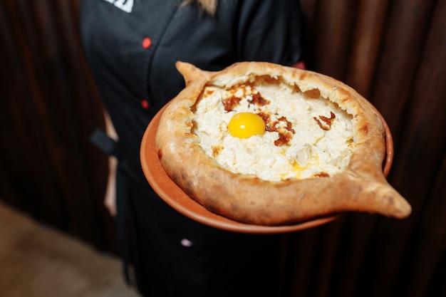 Vue de dessus sur le savoureux khachapuri traditionnel d'adjarie - tarte au four avec du suluguni au fromage salé fondu et du jaune d'oeuf sur un plateau en bois. cuisine géorgienne traditionnelle
