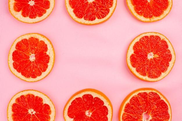 Vue de dessus de savoureux pamplemousses en tranches de fruits juteux bordés sur la surface rose