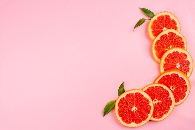 Vue de dessus de savoureux pamplemousses tranches de fruits juteux sur la surface rose