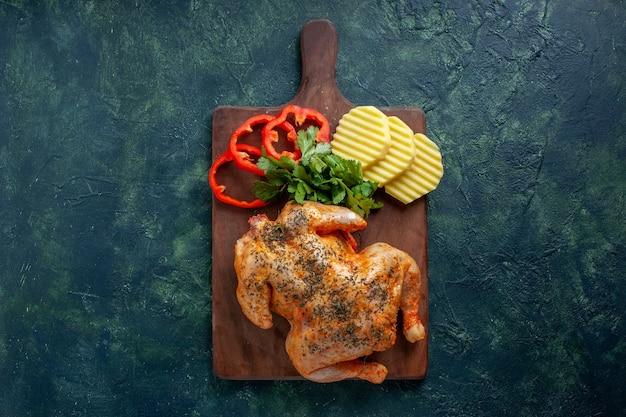 Vue de dessus savoureux poulet cuit épicé avec des pommes de terre et du poivre tranché sur fond sombre plat de couleur de viande dîner repas nourriture barbecue