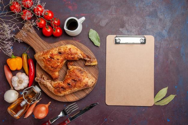 Vue de dessus savoureux poulet frit avec des légumes frais et des assaisonnements sur fond sombre nourriture poulet repas légumes viande