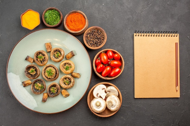 Vue de dessus savoureux repas de champignons avec tomates fraîches et assaisonnements sur le plat de surface sombre dîner repas cuisson champignon