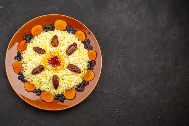 Vue de dessus savoureux repas oriental célèbre composé de riz cuit et de raisins secs dans l'obscurité