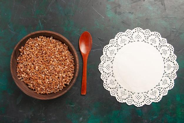 Vue de dessus savoureux repas de sarrasin cuit à l'intérieur de la plaque en bois brun sur la surface vert foncé