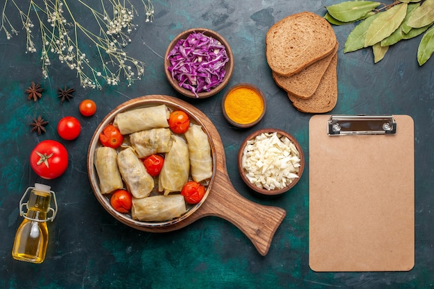 Vue de dessus savoureux repas de viande roulé avec du chou et des tomates appelé dolma avec du pain et de l'huile d'olive sur un bureau bleu foncé