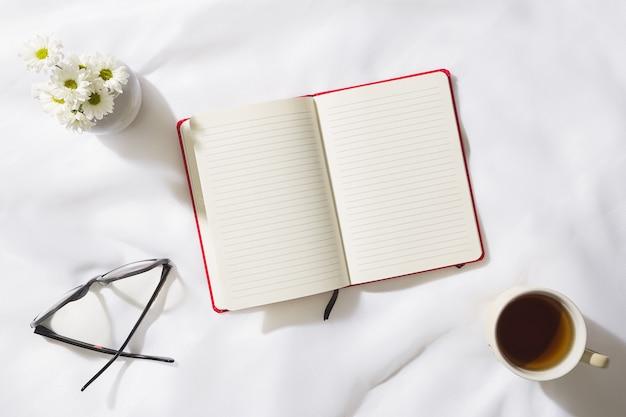 Vue de dessus de la scène du matin en fond de tissu de voile avec un cahier rouge au milieu, des verres, une tasse de thé et un vase de fleurs blanches, avec un espace pour le texte
