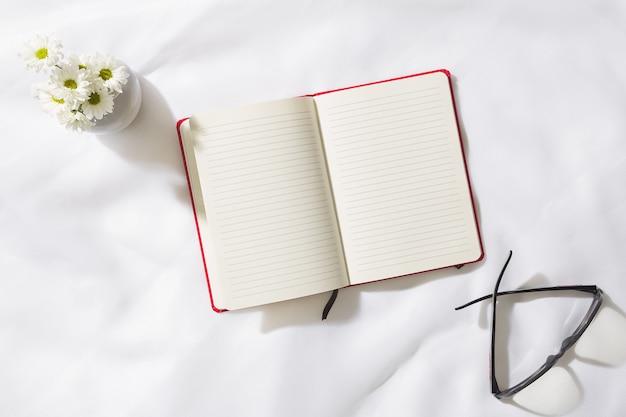 Vue de dessus de la scène du matin en fond de tissu de voile avec un cahier rouge au milieu, des verres et un vase de fleurs blanches, avec un espace pour le texte