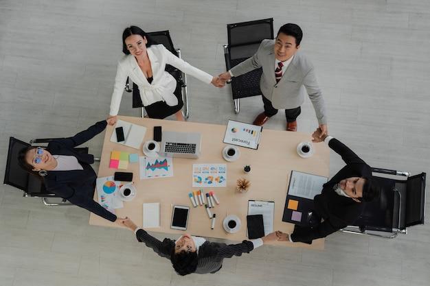 Vue de dessus de la scène des hommes d'affaires de la diversité avec des vêtements de cérémonie debout et tenant la main ensemble autour de la table de réunion une action heureuse pour le travail d'équipe dans un lieu de travail moderne, groupe d'affaires de personnes, concept d'unité