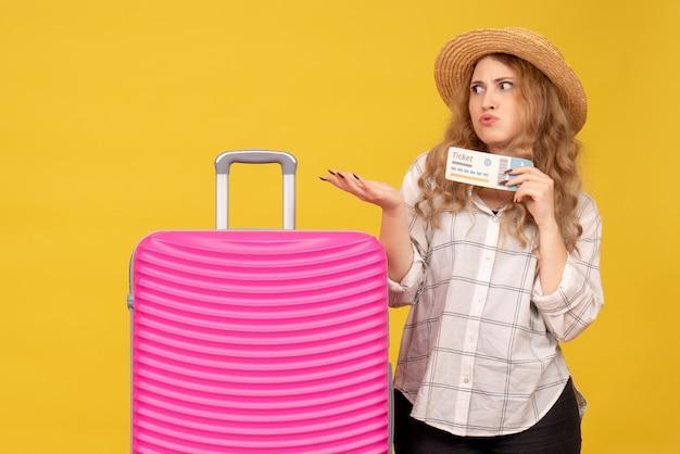 Vue de dessus de se demander jeune femme portant un chapeau tenant un billet et debout près de son sac rose