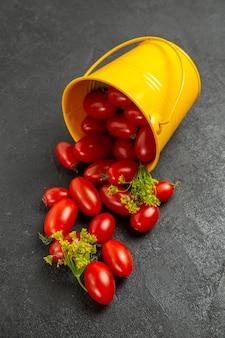 Vue de dessus seau jaune renversé rempli de tomates cerises et de fleurs d'aneth sur le sol sombre