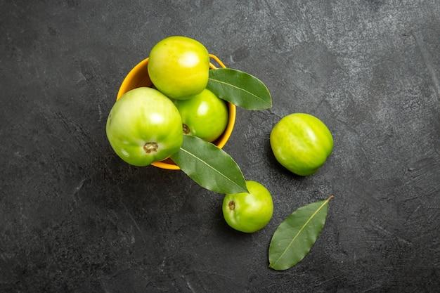 Vue de dessus seau de tomates vertes et de feuilles de laurier et de tomates sur fond sombre