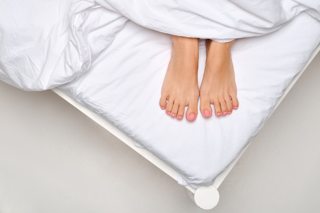 Vue de dessus des semelles féminines qui sortent de sous la couverture