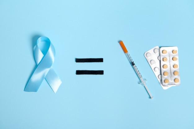 Vue de dessus de la seringue à insuline et du blister avec des pilules médicales sur fond bleu, signe égal et ruban bleu, symbole de la journée mondiale de sensibilisation au diabète. espace de copie pour la publicité médicale. 14 novembre
