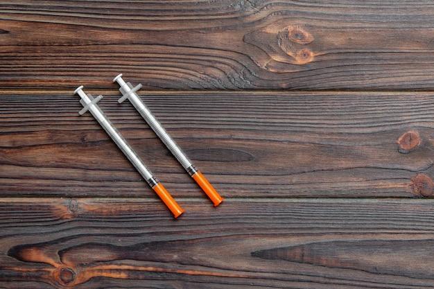 Vue de dessus de la seringue à insuline préparée pour l'injection à fond en bois