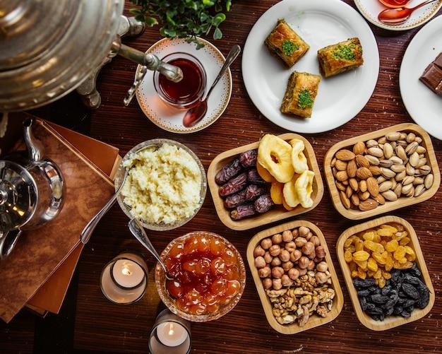 Vue de dessus un service à thé samovar de bonbons confiture de pistaches aux fruits secs baklava avec un verre de thé armudu