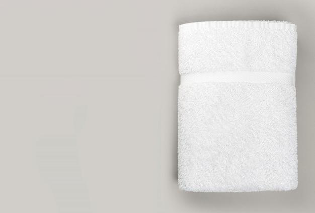 Vue de dessus de la serviette de bain blanche propre pliée sur fond gris avec copie espace
