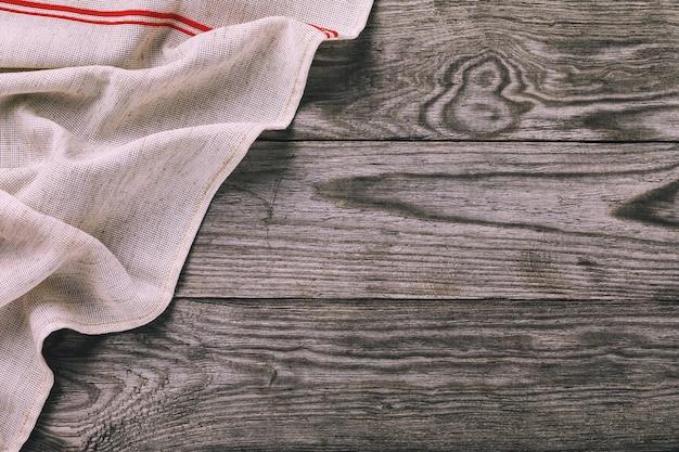 Vue de dessus d'une serviette grise sur le côté gauche d'une table en bois