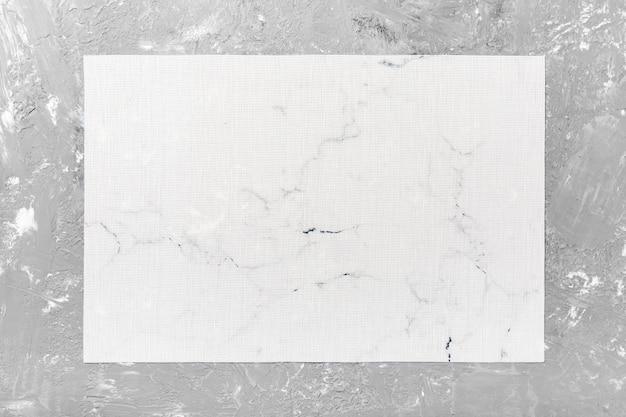 Vue de dessus de la serviette de table blanche sur fond de ciment. placez le tapis avec un espace vide pour votre conception