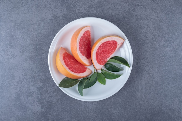 Vue de dessus si pamplemousse frais avec des feuilles dans une assiette blanche.
